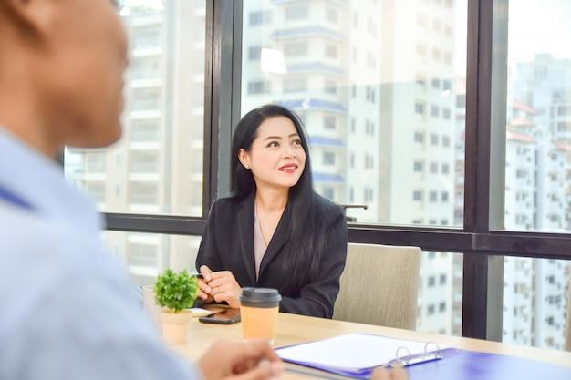 Bedrijfsvrouwen die in vergaderzaal zitten