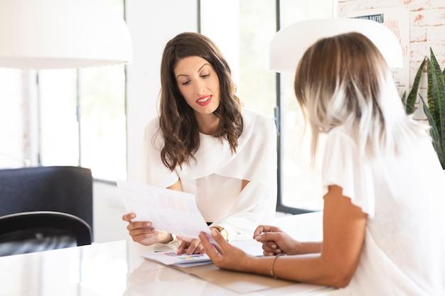 Bedrijfsvrouwen die middelgroot schot samenwerken