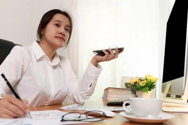 Bedrijfsvrouwen die slimme telefoon houden om met de luidsprekertelefoon te spreken en notities maken op het bureau op kantoor. mensen uit het bedrijfsleven bellen voor het werken met klant of partner met slimme telefoon. bedrijfsconcept.