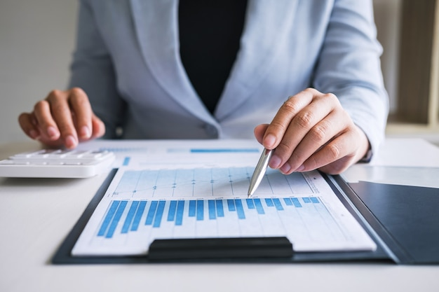 Bedrijfsvrouwenaccountant die controle werken en de balansverklaring berekenen van het uitgaven financiële jaarlijkse financiële rapport, die financiën doen die nota's op papier maken die document controleren