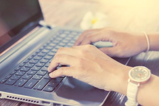 Bedrijfsvrouwenhand die aan laptop werken
