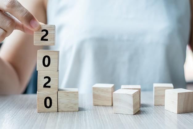 Bedrijfsvrouwenhand die houten kubus met het woord van 2020 houden