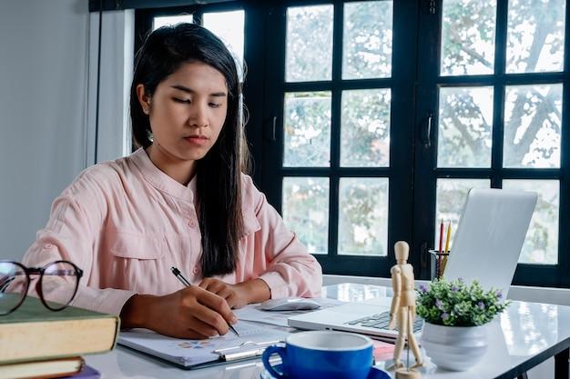 Bedrijfsvrouwenhand die met financiële gegevens en calculator op wit bureau in modern weg werken