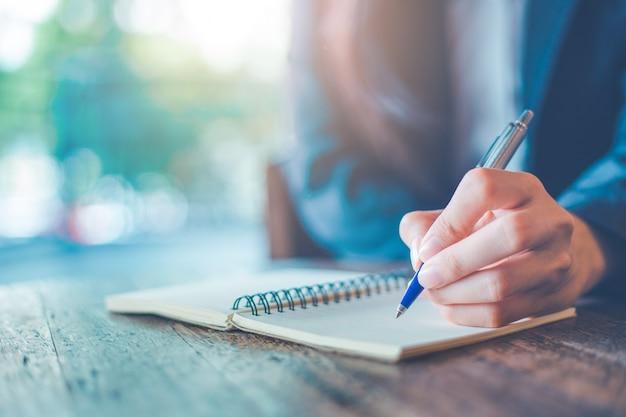 Bedrijfsvrouwenhand die op een blocnote met een pen in het bureau schrijven.