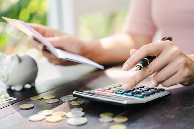Bedrijfsvrouwenhanden die het bankboekje van de spaarrekening met calculator, rekening en besparingsconcept houden.