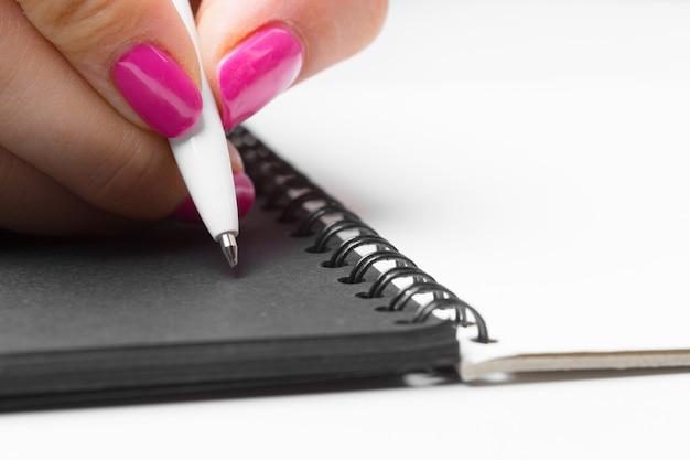Bedrijfsvrouwenhanden die het schrijven notitieboekje werken