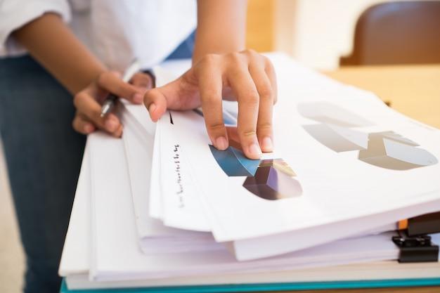 Bedrijfsvrouwenkantorencontrole die voor grafiek het schikken werken