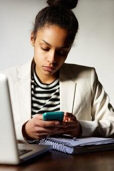 Bedrijfsvrouwenzitting bij bureau met mobiele telefoon