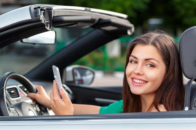 Bedrijfsvrouwenzitting in auto en het gebruiken van haar smartphone.