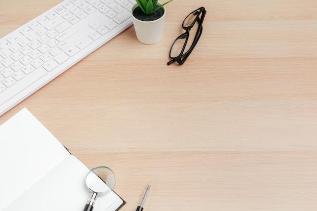 Bedrijfswerkplek met apparatuur op houten bureau, bovenaanzicht
