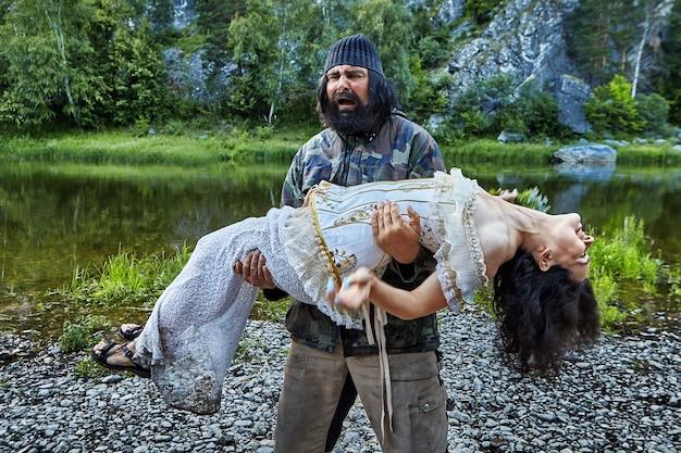 Bedroefd brute oudere man houdt in zijn armen een roerloze vrouw in een avondjurk op de achtergrond van de steenachtige oever van de wilde, bosrivier in het wild. de oude man redt een hulpeloze dame.
