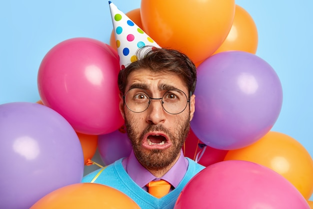 Bedroefd ontevreden man omringd door partij ballonnen poseren