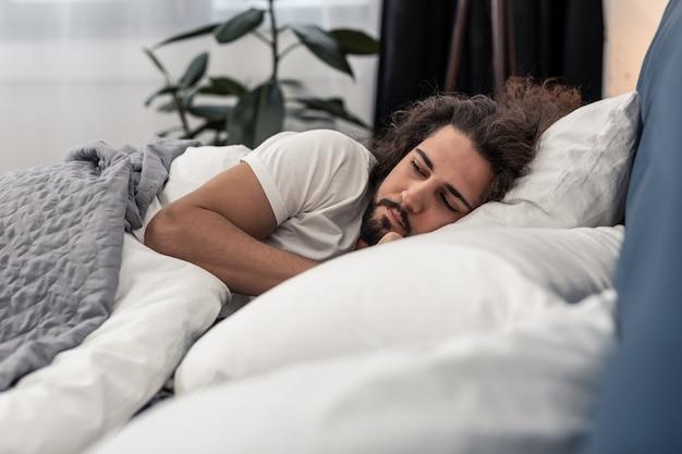 Bedtijd. knappe bebaarde man die 's nachts in zijn slaapkamer ligt te slapen