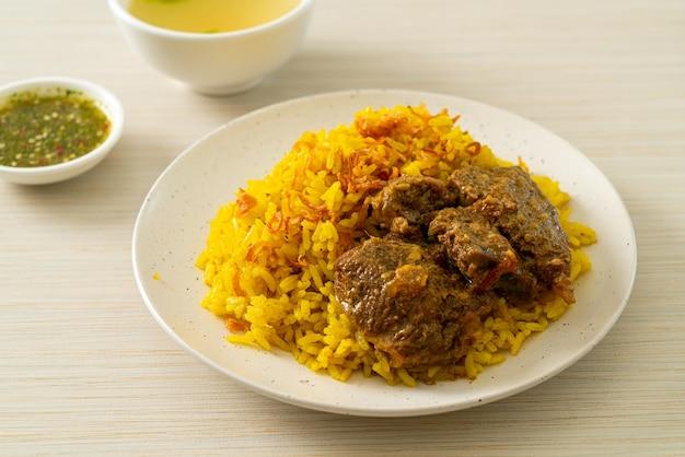Beef biryani of kerrie rijst en rundvlees. thais-islamitische versie van indiase biryani, met geurige gele rijst en rundvlees. moslim eetstijl Premium Foto