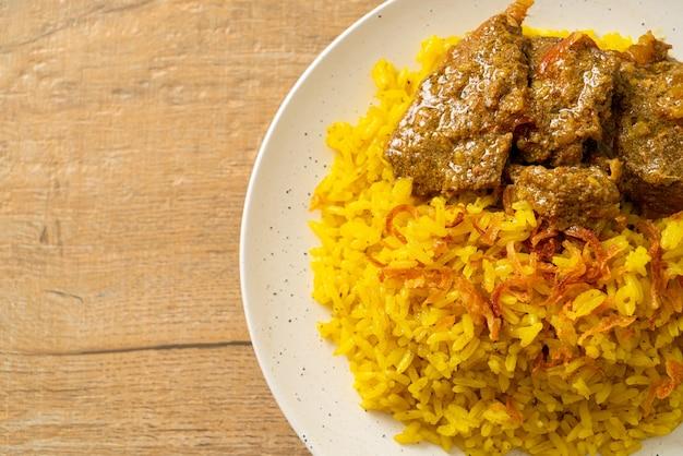 Beef biryani of kerrie rijst en rundvlees. thais-islamitische versie van indiase biryani, met geurige gele rijst en rundvlees.