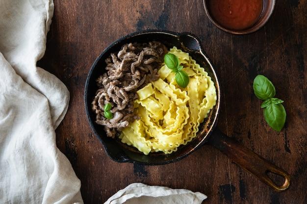 Beef stroganoff in een pan op donkere rustieke houten.