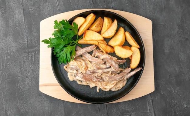 Beef stroganoff met gebakken aardappelen. gegarneerd met peterselie. geserveerd in een pan. uitzicht van boven. grijze betonnen achtergrond.