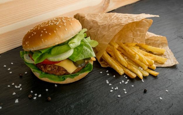 Beefburger met frietjes op zwarte achtergrond