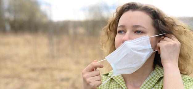 Beëindiging van isolatie en quarantaine corona virus covid-19 concept. een jonge vrouw verwijdert een medisch masker van haar gezicht en ademt frisse lucht in de natuur buiten. banner