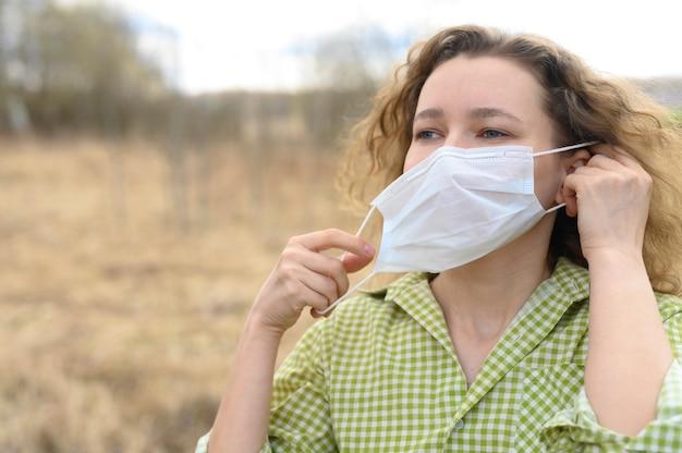 Beëindiging van isolatie en quarantaine corona virus covid-19 concept. jonge europese vrouw van 30 jaar verwijdert een medisch masker van haar gezicht en ademt frisse lucht in de natuur buiten