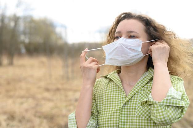 Beëindiging van isolatie en quarantaine corona virus covid-19 concept. jonge europese vrouw verwijdert een medisch masker van haar gezicht en ademt frisse lucht in de natuur buiten