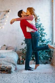 Beeld dat jong paar toont dat en tijdens kerstmis koestert kust