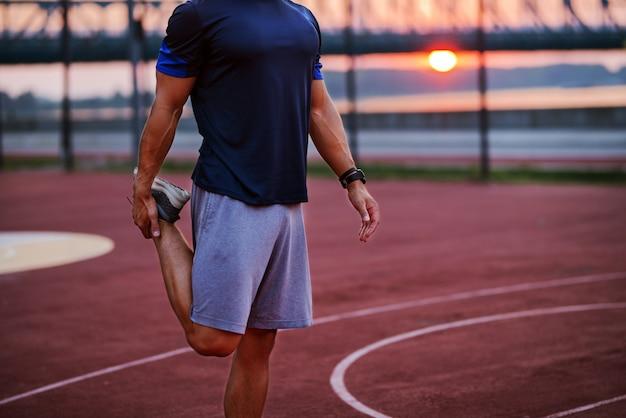 Beeld dat van de spier geschikte mens zijn benen uitrekt vóór harde opleiding. buiten training bij rivier.