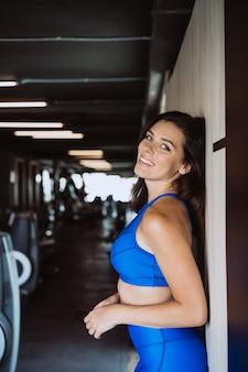 Beeld dat van gelukkig sportenmeisje zich over muur bevindt. camera kijken. vrouw rust na fitness.