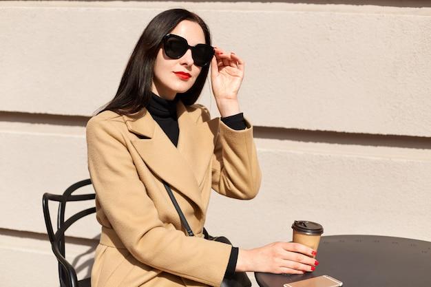 Beeld die van aanbiddelijk modieus jong leuk wijfje haar zwarte zonnebril met vingers wat betreft, genietend van zonnige dag in openlucht, houdend papercup van koffie, zittend bij lijst over lichte muur.