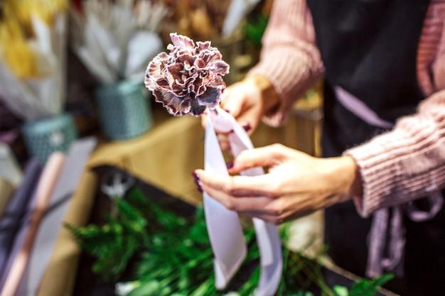 Beeld die van de handen van de vrouw kleine bloemen strak met violet lint houden. ze staat in een kamer vol met planten.