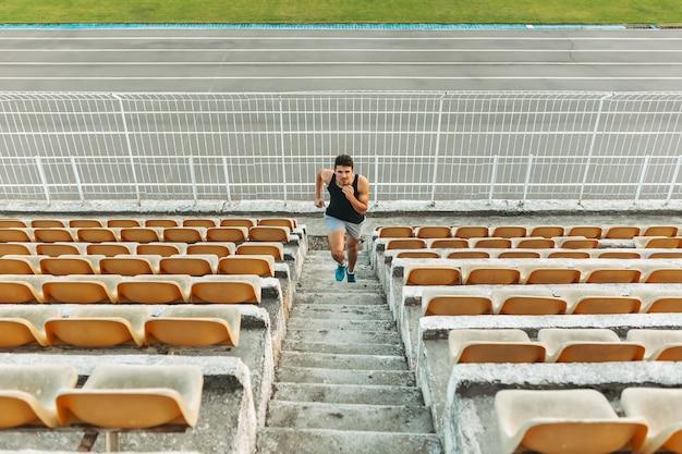 Beeld die van de jonge atletische mens door ladder bij het stadion uit lopen
