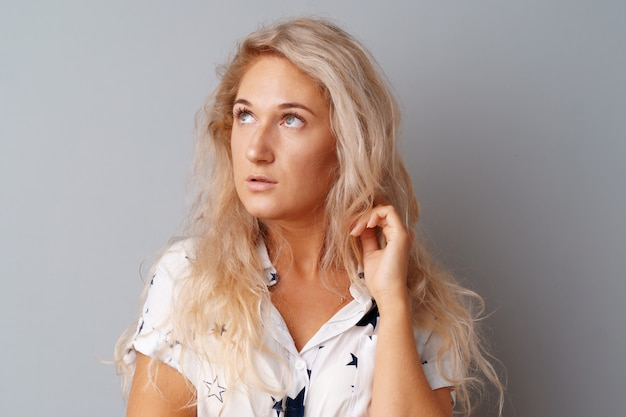 Beeld die van denkende jonge vrouw zich over een grijze achtergrond bevinden