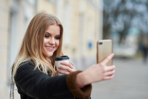 Beeld die van mooie vrouwen meeneemkoffie in document kop houden en selfie nemen terwijl het lopen door stadsstraat