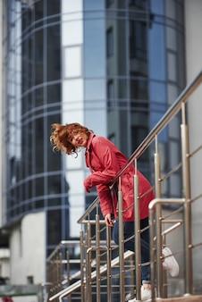 Beeld in beweging. volwassen mooie vrouw in warme rode jas wandelt in het weekend door de stad