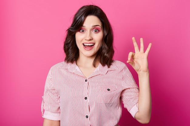 Beeld van aantrekkelijk modieus donkerbruin meisje in gestreept overhemd dat camera met geopende mond bekijkt en ok gebaar toont