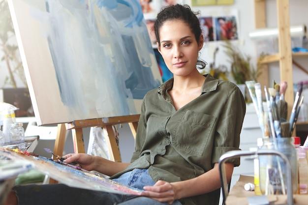 Beeld van aantrekkelijk professioneel jong kaukasisch wijfje die in vrijetijdskleding palet houden en mes schilderen die aan olieverfschilderij werken, kleuren mengen, die uitdrukking op haar gezicht hebben geïnspireerd