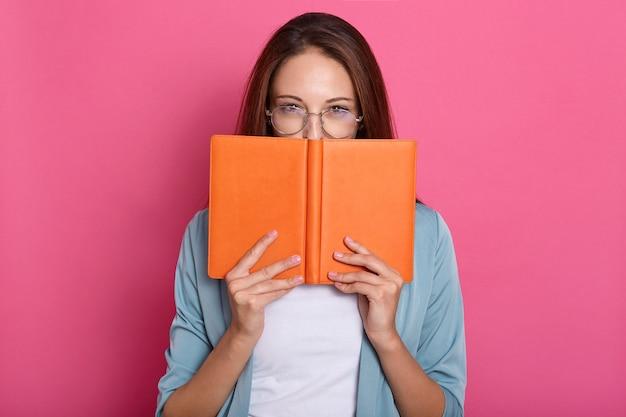 Beeld van aantrekkelijke knappe zoete boekenworm die de helft van haar gezicht met boek behandelt