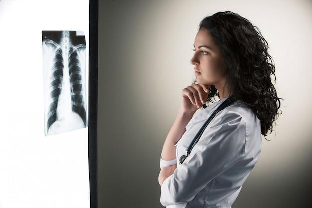 Beeld van aantrekkelijke vrouw arts die x-ray resultaten bekijkt