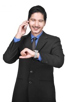 Beeld van aziatische zakenman met cellphone terwijl het bekijken horloge