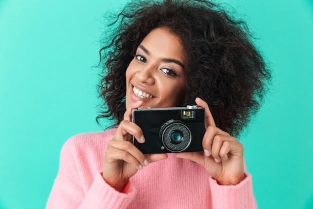Beeld van blij volwassen meisje met retro camera in handen stellen, geïsoleerd tegen blauwe muur