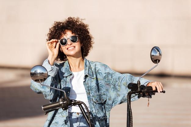 Beeld van blije krullende vrouw die in zonnebril op moderne motor in openlucht zit
