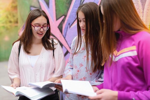 Beeld van boom jonge schoolmeisjes die in schoolbinnenplaats zitten en spreken. boeken op schoot houden.