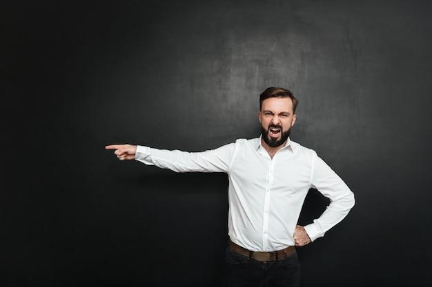 Beeld van boze mannelijke werkgever die in verontwaardiging gilt en vinger op deur richt om over donkergrijs weg te gaan