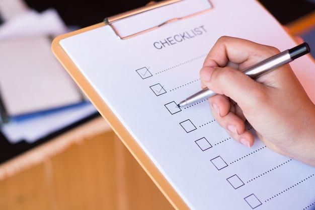 Beeld van businessfemale die controlelijst voorbereiden bij bureau