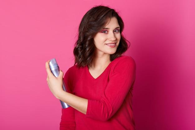 Beeld van charmante glimlachende vrouw die haar haar omhult, haarstyling doet, mooi wil zijn op daten, een casual rode trui draagt, prettige gezichtsuitdrukking heeft, naar de camera kijkt, poseert in een fotostudio.