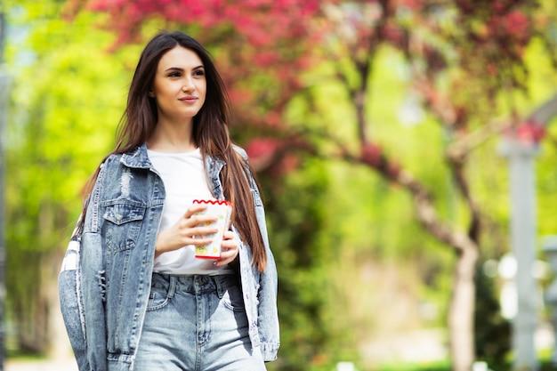 Beeld van charmante vrouw die jeanskleren dragen die popcorn, op pretparkachtergrond houden. reclame voor de vervaardiging van popcorn. mooi meisje voor bioscoopbord. horizontaal.