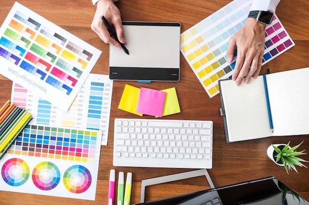 Beeld van creatieve grafische ontwerper die aan kleurselectie werken en grafiekstablet trekken op het werk