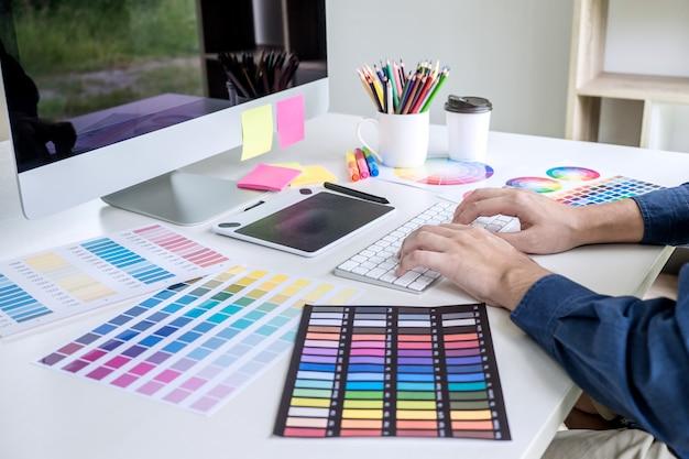 Beeld van creatieve grafische ontwerper die aan kleurselectie werken en op grafiektablet trekken