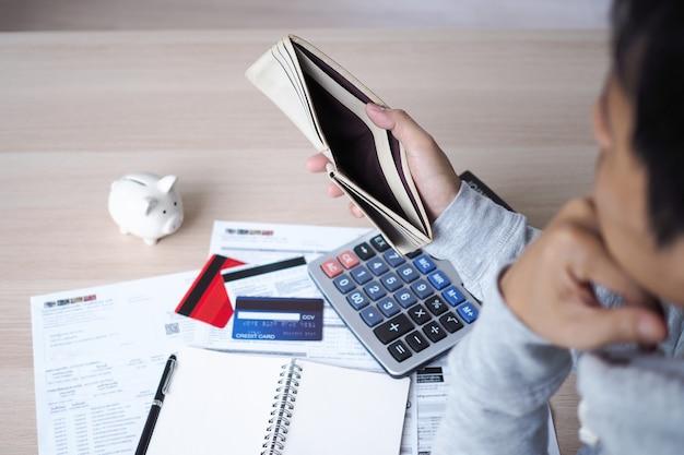 Beeld van de aziatische mens met financiële zorgen die een lege beurs dragen. nadenken over het afbetalen van creditcardschulden, huurwoningen en gezinsuitgaven. financieel probleem en schuldconcept