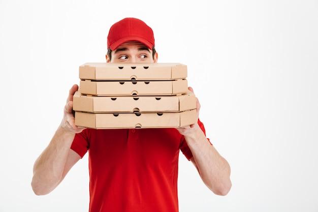 Beeld van de blije leveringsmens in rood eenvormig behandelend gezicht met stapel pizzadozen en opzij kijkend, geïsoleerd over witte ruimte